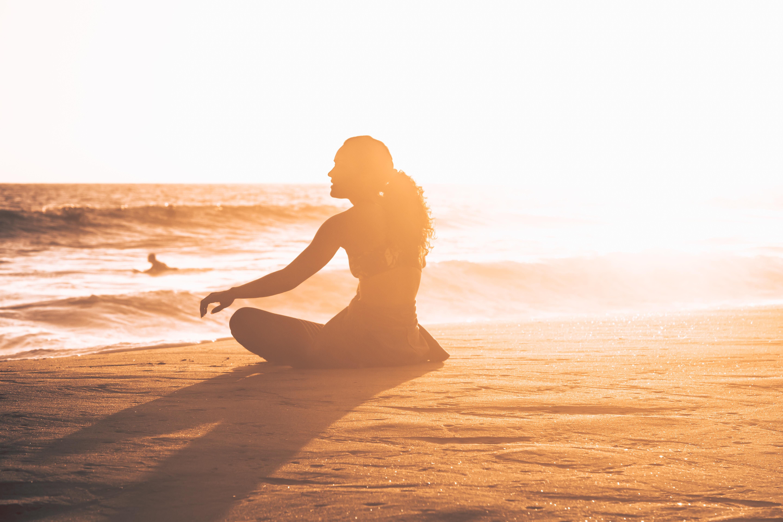 Yoga sur la plage au couché de soleil