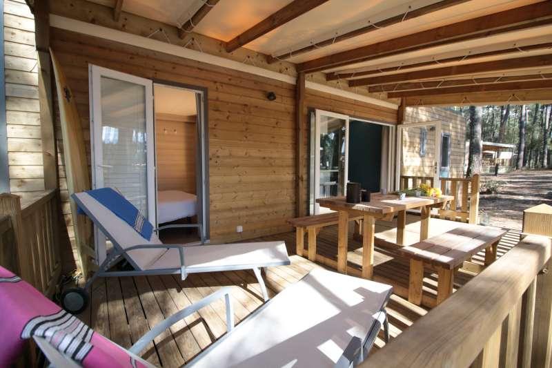 Terrasse en bois avec chaises longues dans la forêt